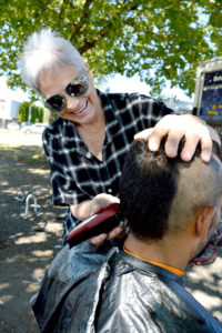 June Ariano-Jakes cuts a man's hair at the corner of 108th Avenue and King George Boulevard. She gives free haircuts to street people twice a week. — Image Credit: Amy Reid