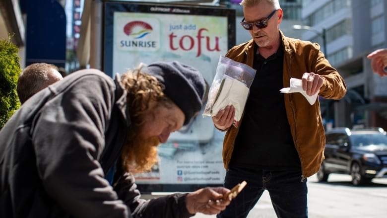 Dan Brown and Kim Maybee hand out food to homeless people in Vancouver, British Columbia on Tuesday, April 30, 2019. (Ben Nelms/CBC)