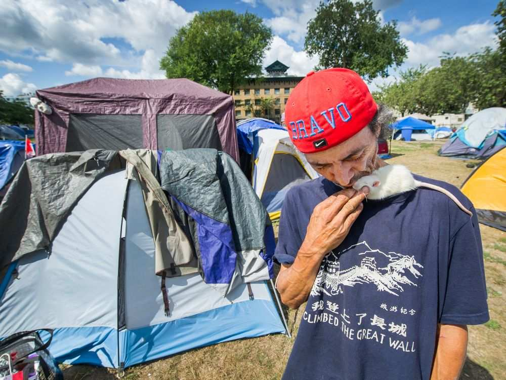 Hector Bravo with his pet mouse Stuart Little at Oppenheimer Park on Monday. He says he's eager to move into social housing after being robbed recently at gunpoint in the tent city. Arlen Redekop / PNG